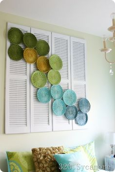 I love the painted plate holders! 3.60 artwork: above bed design using shutters + paper plate holders