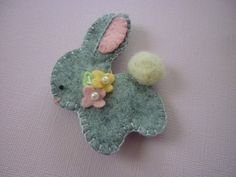Description  Hello,  Welcome and thanks for stopping by !    This Spring bunny pin is a new design this year !  The pin is made from quality light gray wool felt with a white raw wool needle felted tail for extra fluff.    I also added pastel pink and pastel yellow felt flowers with tiny pearl center and mint green felt leaves.    Eye and pink nose are hand embroidered with DMC embroidery thread.    Pin is entirely hand stitched.  The pin back is sewn on NOT glued to the back.    The pin is…