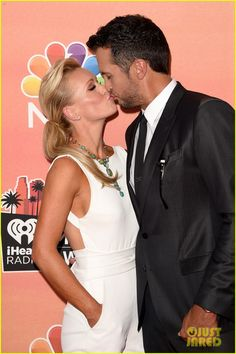 Luke Bryan and his wife Caroline share a cute kiss while walking the red carpet at the 2014 iHeartRadio Music Awards held at the Shrine Auditorium on Thursday (May 1) in Los Angeles.  The 37-year-old singer received two nominations this year – both in the Country Song of the Year category