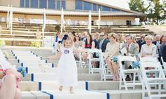 The Flower Girl paves the way with petals on the custom white and blue aisle runner | WM Events