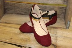 Turn heads with this Faux suede ballet style flat. Black side bow accents the ankle strap on this burgundy shoe.This shoe has a cushioned insole and heel goldtone zipper closure. All man made material. We suggest ordering a half size larger.