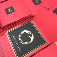 Custom foil logo on matte black card stock in a red pocketfold - all sealed up with a crisp gold foil monogram.
