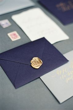 Intricate gold wax seals on dark amethyst envelopes // writtenwordcalligraphy.com