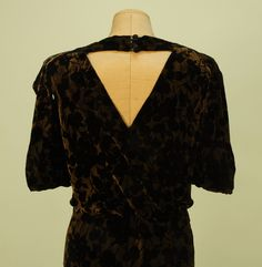 Back Detail VOIDED VELVET and GOLD BIAS CUT EVENING GOWN, c. 1930. Black velvet in an overall pattern of cherries on a metallic gold ground with draped cutout V-back with four self button and loop closures at top, slight cowl front, pointed cap sleeve and unusual looped arm treatment.