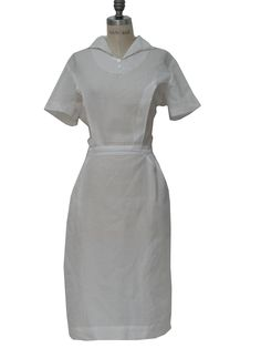 50s -La Grace- Womens white polyester sheer rib knit mid length, short sleeve nurse dress with thin fold over collar, modest v-neckline with three button faux placket, inverted pleating to create down bust princess seaming and empire waistline.