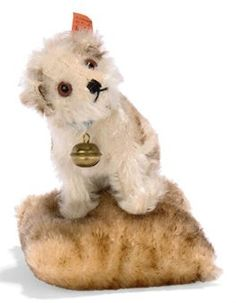 A STEIFF MOLLY ON PINCUSHION, (3368,6), seated, brown tipped white mohair, brown and black glass eyes, black stitching, ribbon with bell, brown tipped mohair cushion and FF button with red cloth tag numbered 3310, circa 1930 --5¼in. (13.5cm.) high (some fading)