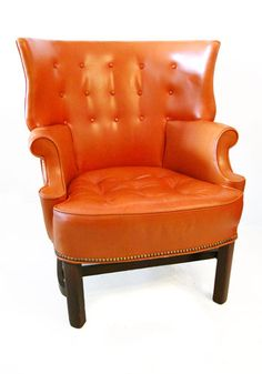 Great decorative orange leather club chair from the late forties. Solid walnut legs with brass stud accents.