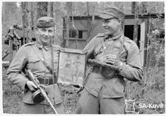Finnish soldiers with m/31 Suomi submachine guns (and a pinup photo).   [ photo from http://sa-kuva.fi/ via http://www.forgottenweapons.com/ ]