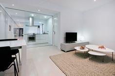 Chiralt Arquitectos I Salón comedor cocina en vivienda moderna con mobiliario minimalista separados por un cristal, dando luz y sensación de espacio interior.