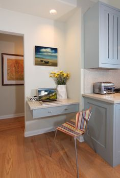 The kitchen office nook with floating desk drawer provides a tidy corner for…
