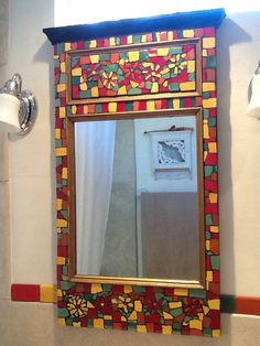 Mosaic mirror with salvaged mirror and Mexican tile.  Matches tile trim in my bathroom. Mosaic by Jan Wolfe.