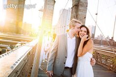 Young couple on Brooklyn Bridge at sunset - gettyimageskorea