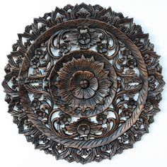 A detailed carving of the Lotus theme in a smaller round size. Several recycled rough-hewn teak planks from old dwellings and community buildings are joined together and then carved as a single unit.