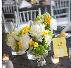 With flags hanging from the ceiling, the couple kept the centerpieces low to the table. Tea lights surrounded square vases of ranunculus, peonies, cymbidium orchids, and lady's mantle.