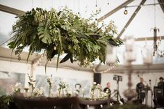 Burgundy and dark green floral display hung from ceiling in