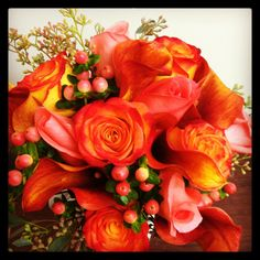 Mango calla lilies, circus and movie star roses, peach hypericum berries and seeded eucalyptus.