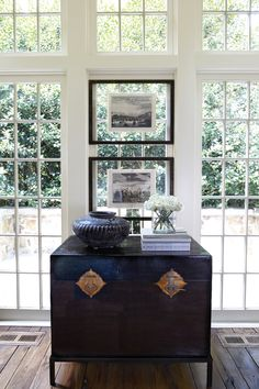 """Hanging Art and placing a chest in front of these windows creates another """"wall"""" in this room...k...creative use of space and a genius idea to float the Art between glass as to leave the view open."""