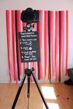 To set up your own photobooth, make a sign instructing your guests on how to use your self-timer. Add a tri-pod and a backdrop and you're good to go!