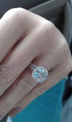 Round brilliant center diamond w/ square halo made up of shared prong set round brilliants on a 3 row split pave shank engagement ring