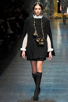 "Dolce & Gabbana 2012 RTW. OMG! There is so much to love about this. Another cape style coat, double-breasted buttons and matching black skirt with a romantic white ruffle blouse...and lace-up boots! My favorite. The earrings are glorious (of course, the matching headdressing) and this ""necklace"" small purse is so fantastic, I WISH I could have one! *sigh* The boots and purse necklace are so gorge, I'm pinning the details photo for both of them."