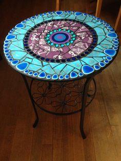 Mosaiktisch mit herausnehmbarer Glasplatte. Die Platte wurde mit Gewebenetz (zwecks Haftung) vorbereitet. Keramikpebbles, Glasnuggets und Knopfmosaik, kombiniert mit alten 70er-Jahre-Fliesen in...