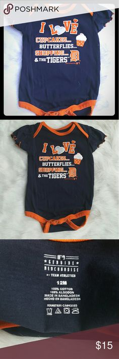 "Detroit Tigers Girl's Onezie Size 12 Mos Genuine Merchandise Team Athletics little girl's onezie dark blue with Tiger's orange outline. Front of outfot wording says ""I love cupcakes, butterflies, shopping and the Tigers."" Team Athletics  One Pieces"