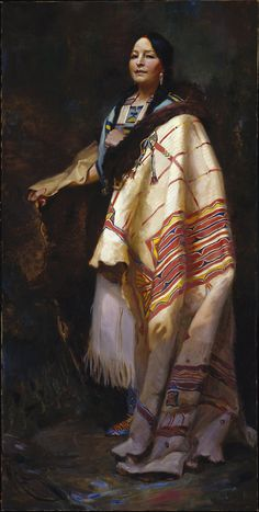 """Harry Edwards painted Handsome Morning—A Dakota in 1921. As the Brooklyn Museum describes, Edwards painted Handsome Morning """"wearing a fringed shift with painted emblems, a bead-and-quill necklace, beaded moccasins, and a ceremonial blanket of fur-lined buffalo hide painted with abstract motifs (a specialty of Dakota women)."""" Edwards picks up the bold colors of her garments in the indistinct strokes of the background, tying the subject and her setting together."""