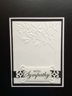"Sympathy card using Spellbinders Fancy Tags die and ""With Sympathy""clear stamp. 5x6.5"" pre-made white card was layered with black card stock and white card stock embossed with Darice - Leafy Tree Trunk embossing folder.  Black satin ribbon was used behind the label and tucked under the white card stock layer. Created by: Melanie Weise"