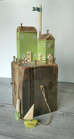 Hergestellt aus altem Holz und Metall, zeigt dieser nordischen Stil Küsten-Hütte Szene zwei Erbsen grüne Hütten auf einem massiven Stück Jahrgang Altholz in die Enge getrieben. Gibt es seitliche Türen und Fenster, ein Rettungsring und Leitern führen bis auf ein paar passende grüne