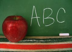 education | Apple sitting on the ledge of a blackboard