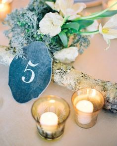 Table numbers were letterpressed onto blue velvet placecards and propped up on branches to complete the centerpieces. Get inspired by viewing more pictures from this wedding online!