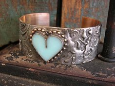 A fun and fabulous boho-chic cuff bracelet thats full of old-world romance!  I think of fossils when I work with hot stamped solder...so I named this bracelet Timeless. My signature heart bezel is filled with tinted jewelers resin in sweet robins egg blue. Two applications of hand-rubbed patina add to its old-world charm, and a generous coat of Renaissance wax protects the finish. These cuffs are loving crafted by me entirely by hand, and due to their handmade characteristics, no two will be…