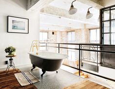 Open bathroom with a clawfoot tub, wood floors, and a simple stool