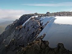 View across rocks, snow and ice to the flat summit of Ben Nevis