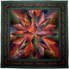 """Jinny Beyer's Quilt """"Sundance"""" glows with an olive green, bright orange, purple and fuchsia palette. Jinny modified an eight-pointed star block and sized it up to 60"""" square. Then she fragmented the star points and background. Careful fabric shading makes the design pulse light and energy."""