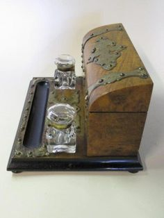 Late 19th, early 20th century. A desk set consisting of a burl wood stationary box, with chased brass mounts and original key, on a base fitted with two lidded glass inkwells and a pen rest.