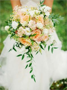 Gorgeous Bridal Bouquet Showcasing: Peach Roses, Peach Stock, White Lisianthus, White/Yellow Chamomile, Green Italian Ruscus Foliage