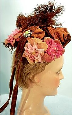 Antique Dress c. 1870's Victorian Bonnet of Brown Velvet, Large Velvet Flowers, Satin Ribbon, Brown Feather and 2 Jeweled Ornaments! De-accessioned from a museum with the original museum tag still dangling. There is a number on the tag of 1897, but that's just a museum number. Hats from the 1870's are the ones that seem to have the long ribbon tails in fashion. Excellent condition with just one pearl missing from one ornament mostly hidden under feather. Comb inside - not original