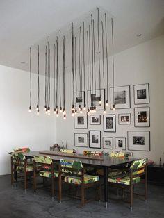 rechteckiger Esstisch, Stühle mit buntem Polster und hängende Industrielampen - Glühbirnen