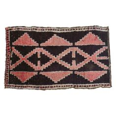 A small but stunning vintage Kars rug, that features a running lattice design and stepped-geometric triangles. The dark, deep background is accented with soft grapefruit red and ivory accents to boot!