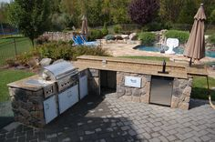 An outdoor oasis: Outdoor kitchen, fridge, cabinets for storage, ontop a paver patio!