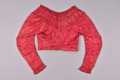 LOT 533 SILK SPENCER, PROBABLY FRENCH, EARLY 19th C. Red floral damask having wide band of center-stitched ruching at neckline and ruffled cuff, hook & eye closures, natural linen lining. B-32, L-13. (Light overall wear) very good. Apparently a MET deaccession.