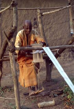 """Guro weaver at work using a carved loom pulley, mid 1980's, Ivory Coast, Africa."" ~ Photo credit ©Eberhard Fischer."