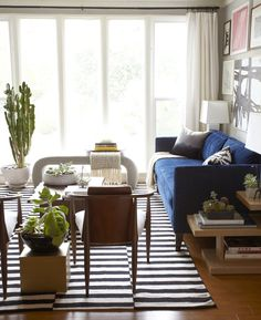 Although the apartment is comprised of mostly neutrals, the blue sofa centers the room with a contemporary touch.  Photo by Zeke Ruelas via Homepolish