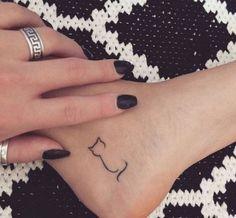 hier ist ein bein und eine ferse mit einem kleinen schwarzen katzen tattoo und eine hand mit einem ring und finger mit einem schwarzen nagellack