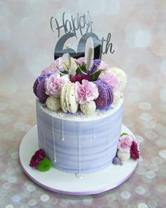 Macaroons, white forerro rocher, carnations, sixty cake topper. Plain cream cheese icing.
