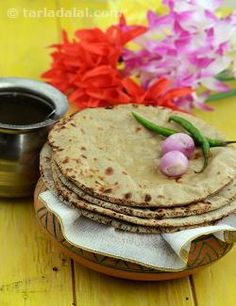 """Though bajra is grown only in certain parts of Rajasthan, bajra rotis are relished all over the state.  Thickly rolled bajra rotis are cooked over """"kanda"""" (cow dung cakes) in the villages. That is the authentic way of preparing them because it imparts a smoked flavour to the rotis.  Bajra rotis can accompany virtually any vegetable or kadhi on a Rajasthani menu. Bajra roti, lahsun ki chutney and onions is the staple diet of the locals.  Although absolutely simple to make, these rotis are ..."""
