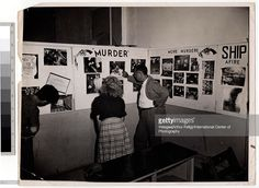 Photography fans examine a series of wall-mounted collages at Weegee's one man exhibition, 'Murder is My Business,' held at the New York Photo League, New York, New York, late 1941. The collages feature such headings as 'Murder,' 'More Murders,' and 'Ship Afire.' (Photo by Weegee (Arthur Fellig) / International Center of Photography / Getty Images)