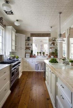 Open galley Kitchen into great room/dining.. Lovely, but I'd need toe kicks under the cabinets or I'd be stubbing my toes continually! Love the flooring too.