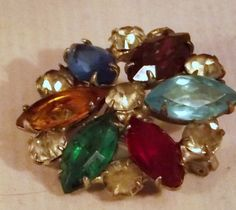 A vintage Fruit salad rhinestone broach. The colors glisten ,turquoise, emerald green, pink, fushia, purple, tourmaline, red, blue and white  An elegant treasure. A family heirloom. Memories of bustling full skirts , frills and lace dresses and sophisticated ladies wearing pearls and rhinestone broa...